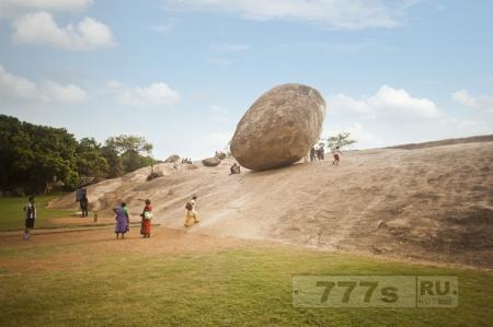 Туристы искушают судьбу, стоя под огромным валуном