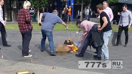 Одежда уличной танцовщицы загорелась от факела, прохожие пытаются потушить ее колой