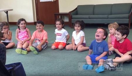 Маленький мальчик не может перестать заразительно смеяться во время музурока