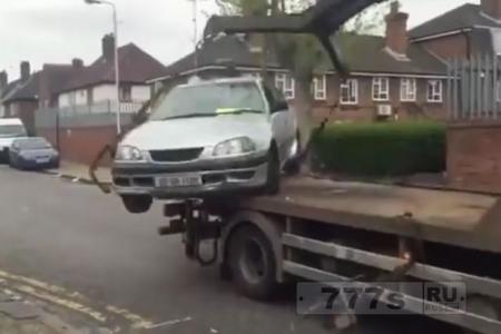Водитель пытается вернуть свой автомобиль уже погруженный на эвакуатор