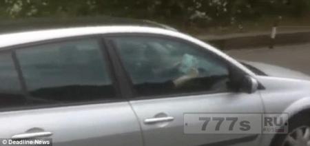 Женщину сфотографировали читающей книгу прислоненную к ее рулю на автостраде