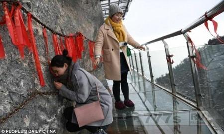 Туристы в ужасе пробираются по дорожке с прозрачным дном на высоте 2250 метров.