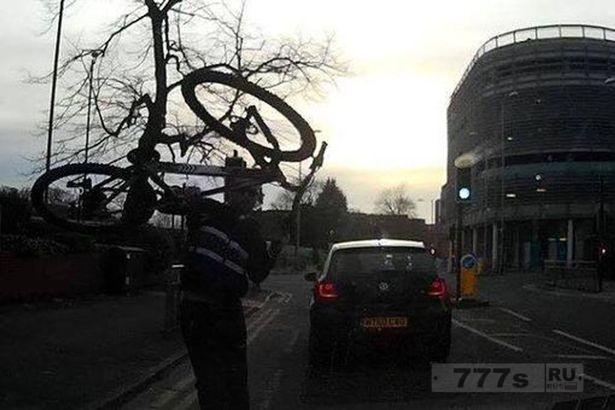 Разъяренный велосипедист бросает свой велосипед на лобовое стекло машины женщины.
