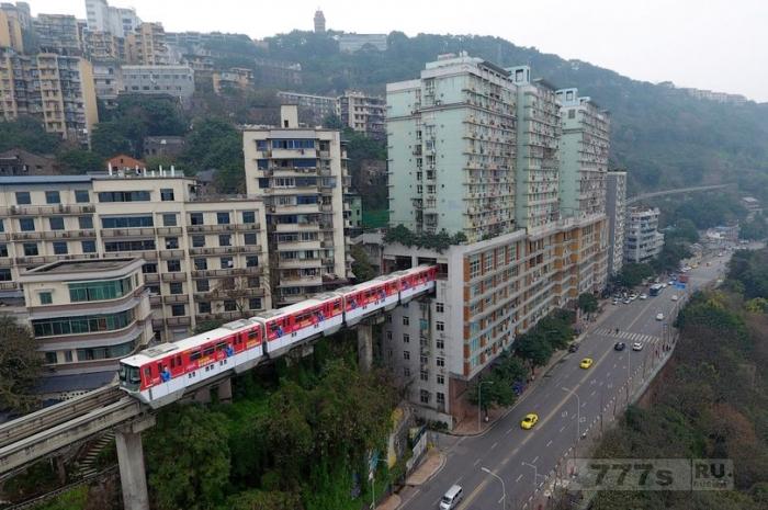 На удивительных фотографиях китайский поезд идет через жилой дом.