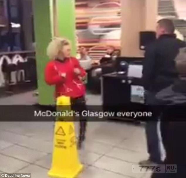 Маленькая шотландская женщина избивает мужчину намного выше ее в Макдональдс.