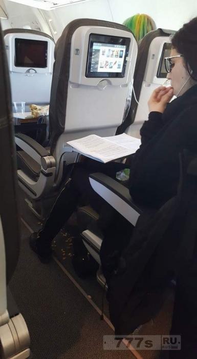 Пользователи возмущены женщиной, сфотографированной за поеданием фисташек и бросанием скорлупок на пол самолета.
