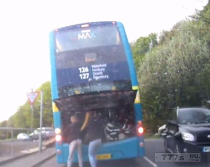 Два подростка открывают заднюю панель двигателя двухэтажного автобуса и нажимают его кнопку экстренного выключения двигателя.