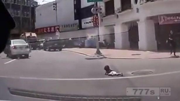 Малыш вываливается из машины, так как ему удалось открыть дверь.