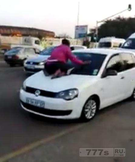 Интересный момент обиженная женщина залазит на ветровое стекло машины мужа.