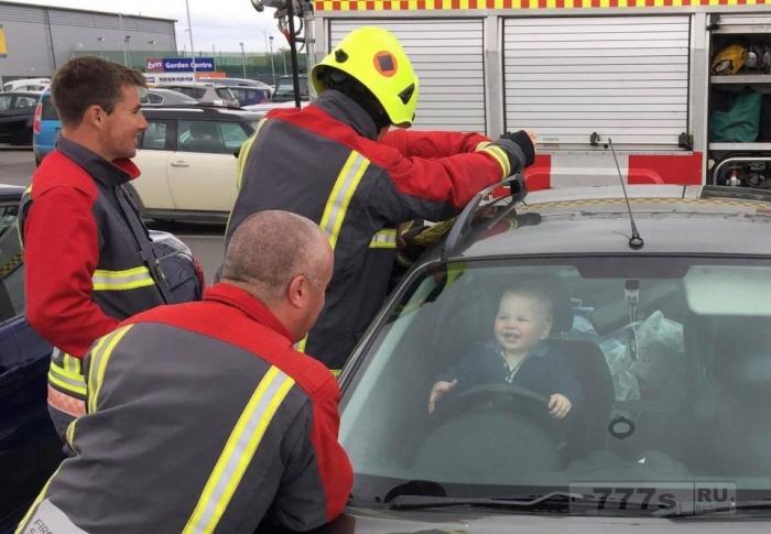 Малыш закрыл себя в машине мамы и радуется, когда пожарный развлекает его, а его напарники пытаются освободить его.