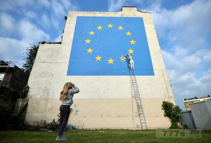 Новая картина художника Бэнкси показывает, как уборщик счищает одну из звезд на флаге Евросоюза.