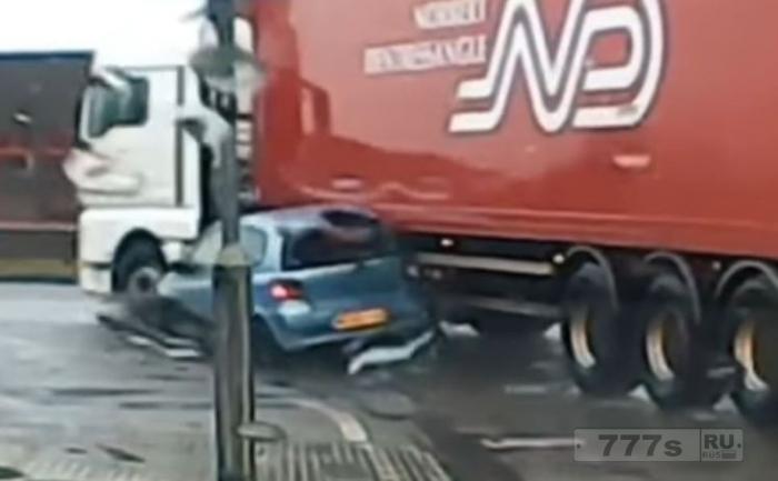 Автомобиль был раздавлен грузовиком на повороте.