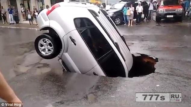 Легковой автомобиль провалился в глубокую яму, которая обраховалась посреди оживленной дороги.