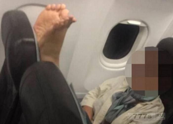 Пассажир самолета стыдит попутчика, который поставил босые ноги на спинку сиденья.