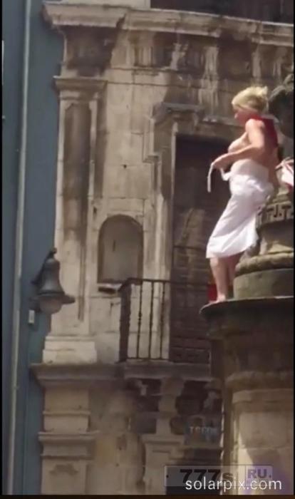 Девушка поднимается на фонтан города Памплона, распахивается и прыгает вниз в толпу поклонников на фестивале Сан-Фермин 2017.