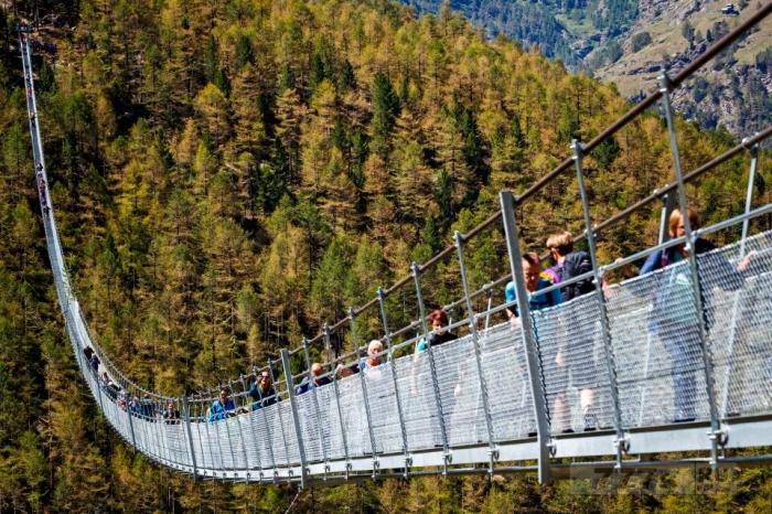 Снимки, вызывающие сосание в желудке, показывают, как храбрые туристы идут по висячему швейцарскому туристическому мосту.