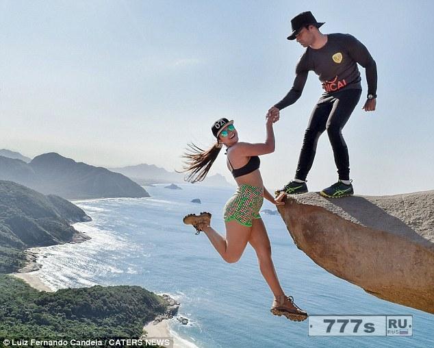 Смельчак, похоже, болтается над краем обрыва в Бразилии, а рука ее жениха удерживает ее от падения ... но все не так, как кажется