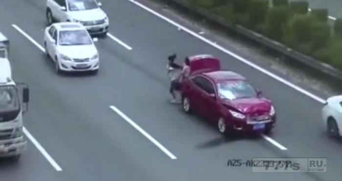 Пара, держащая ребенка, едва избегает быть убитой, когда они уворачиваются от машины, врезающуюся их разбитую машину.