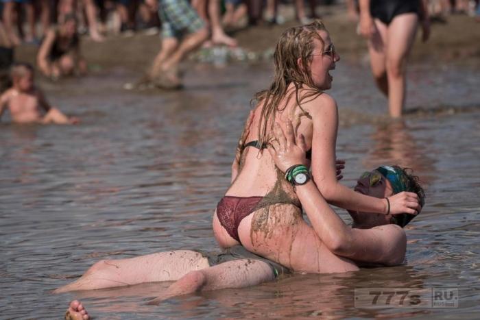 Голые девушки валяются в грязи на музыкальном фестивале Вудсток в Польше.