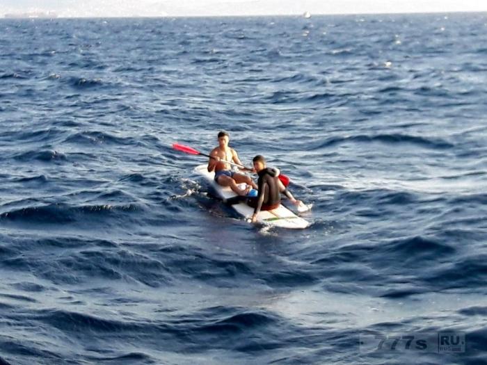 Два молодых мигранта пытаются пересечь пролив из Марокко в Испанию на доске для серфинга.