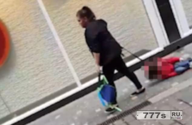 Женщина тащит мальчика по улице в Ливерпуле.