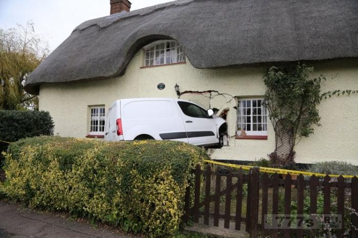 Белый фургон пробил стену коттеджа с соломенной крышей.