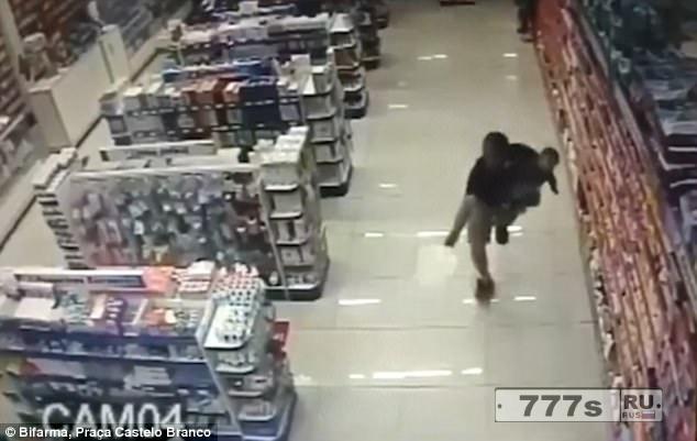 В неслужебное время полицейский с ребенком в руках застрелил двух грабителей, когда они грабили аптеку.