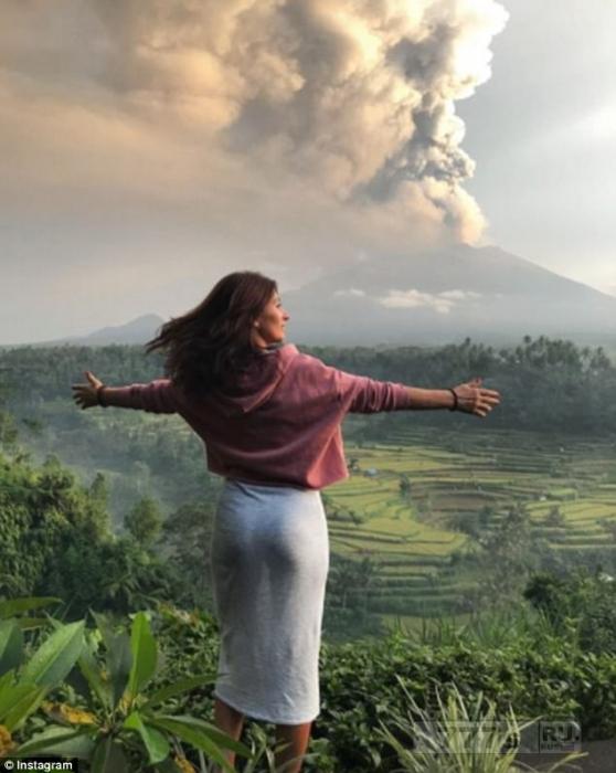 Туристы позируют в бикини перед извержением вулкана Агунг на Бали.