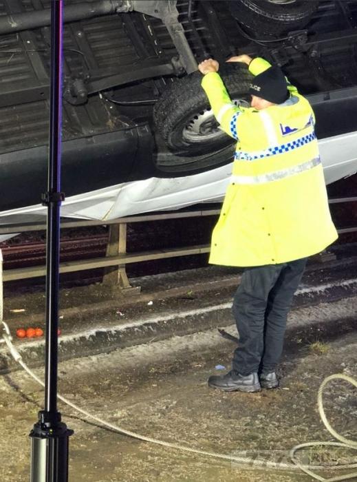 Герой-полицейский уцепился за грузовик, висящий над мостом, используя только голые руки, чтобы спасти водителя