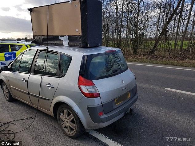 Водитель остановился на оживленной дороге с небольшим диваном, привязанным к крыше его машины