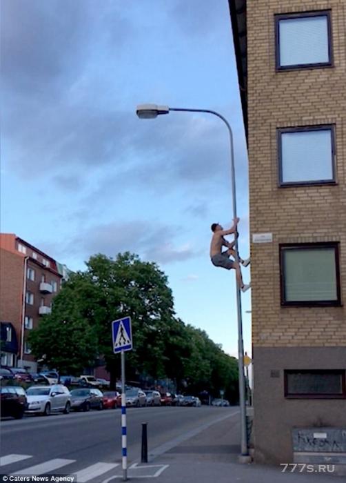 Пожарный без майки залез на фонарный столб и выполняет подтягивание, когда он болтается в 6 метрах от земли