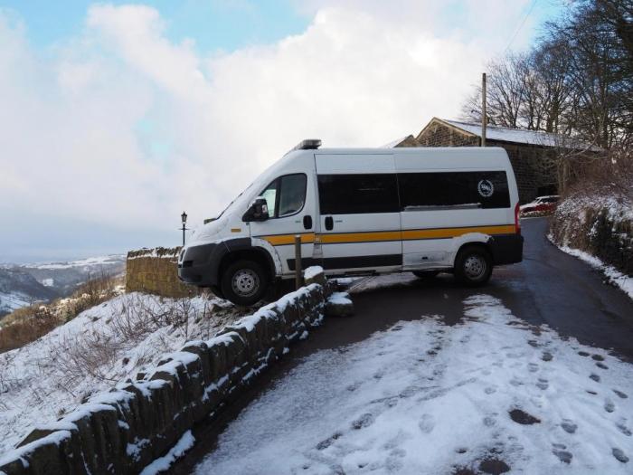 Скорая помощь покачивается по краю обрыва после пробивания через стену в снегу