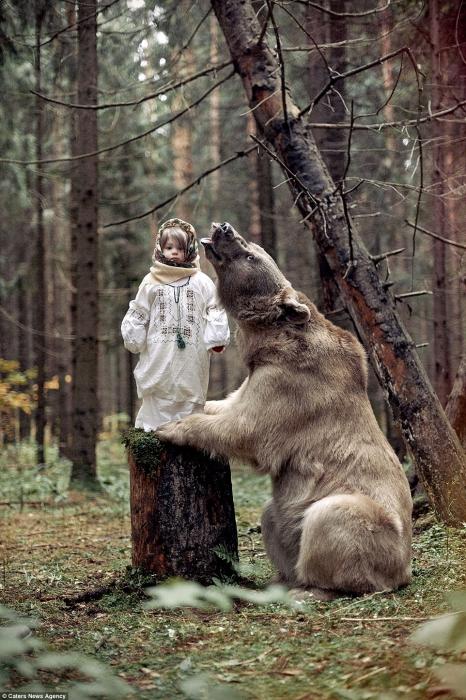 Маленькая девочка позирует с 317-килограммовым медведем гризли после того, как он был взят в семью еще детенышем