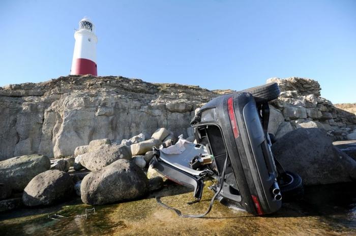 Спасатели торопятся достать мужчину из машины до прилива, упавшей с высоты 8 метров на скалы