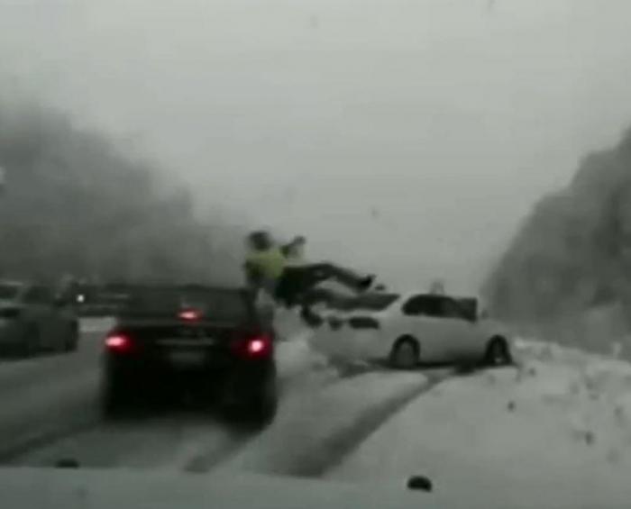 Американский полицейский был сбит автомобилем, потерявшим управление и отброшен в другое транспортное средство на ледяной дороге