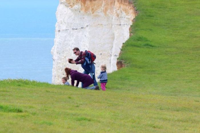 Родители позволяют малышам позировать для фотографии на более чем 150-метровом опасном утесе