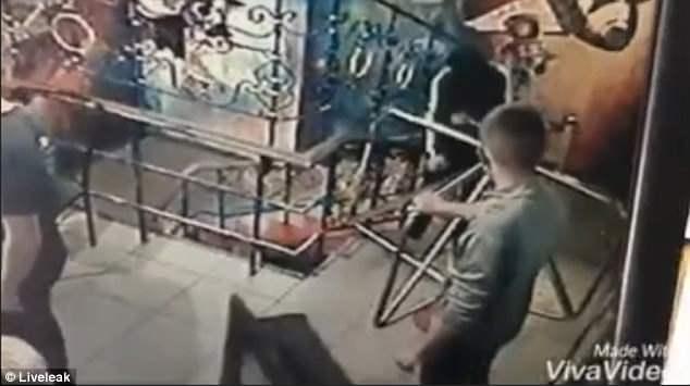 Мужчина в балаклаве, бросает гранату в ночной клуб, люди спасаются бегством, когда она взрывается и сильно ранит восемь человек