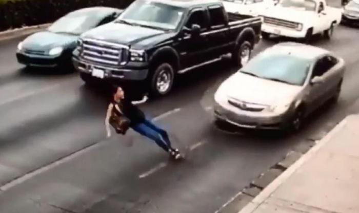 Шокирующий момент женщина, бегущая по оживленной дороге на высоких каблуках, поскальзывается и падает под машину