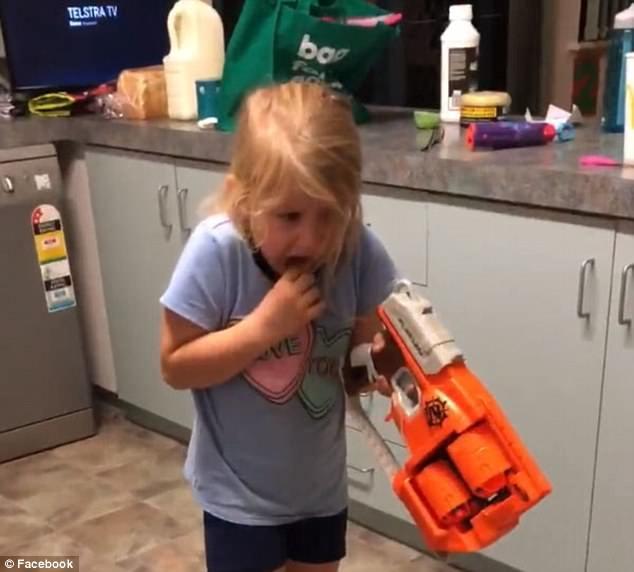 Родители храброй маленькой девочки присоединяют ее шатающийся молочный зуб с игрушечным бластером ниточкой. Девочка вырывает зуб нажав на курок