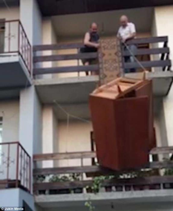 Двое мужчин пытаются спустить шкаф из квартиры второго этажа ... но все заканчивается не очень хорошо