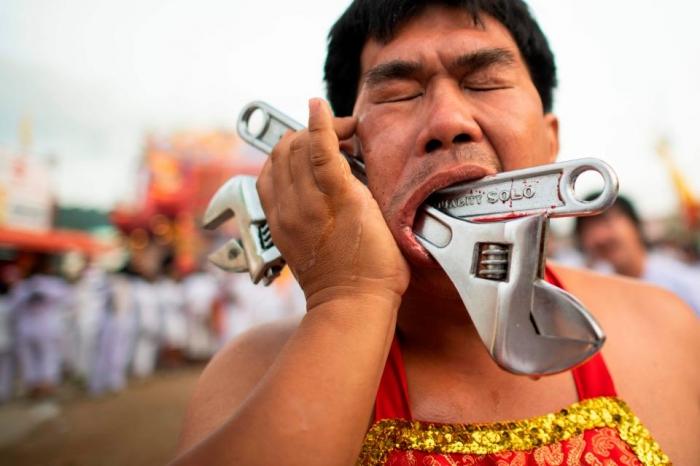Кровавые фото показывают, как участники фестиваля пронзают свои щеки металлическими прутьями, гаечными ключами и бензиновыми насосами