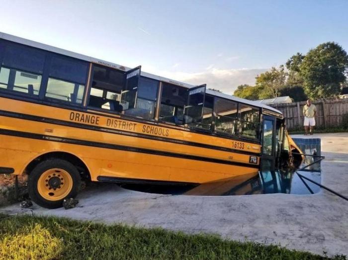 Желтый школьный автобус, перевозящий малышей въехал в плавательный бассейн после того, как машина, объезжала кошку