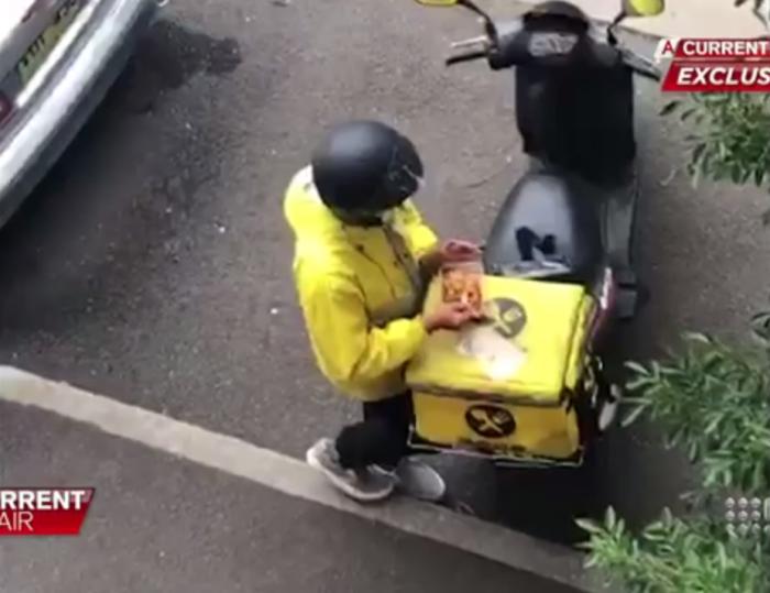 Водитель службы доставки был снят за едой пищи, которую он доставляет, после чего он встряхнул контейнер, чтобы выглядел полным