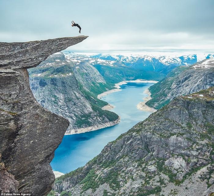 Смельчак выполняет сальто и другие храбрые трюки на скалистом языке знаменитого норвежского тролля