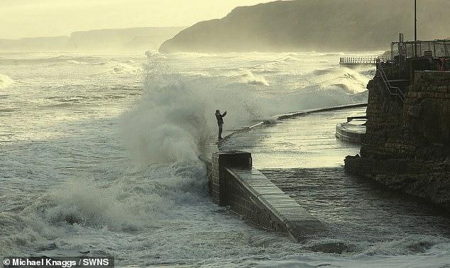Шок! Мужчина рискует своей жизнью для селфи на узком выступе, когда волны 3,5 м высотой падают ему на голову