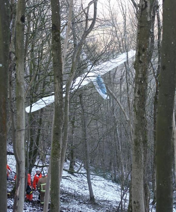При помощи вертолетной лебедки снимают пилота из его планера, застрявшего на высоте 30 метров в деревьях