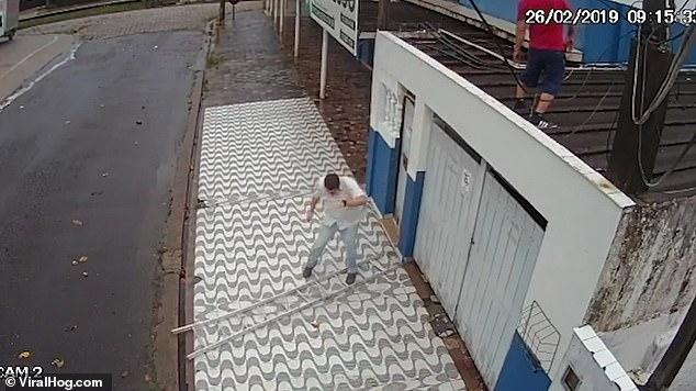 Невозмутимый рабочий приземляется на обе ноги после того, как лестница уходит из-под него, когда он поднимается на гараж