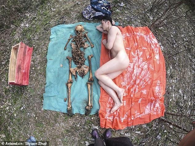 Китайский художник лежит голым рядом с останками своего отца после того, как выкопал скелет из его могилы для фотосессии