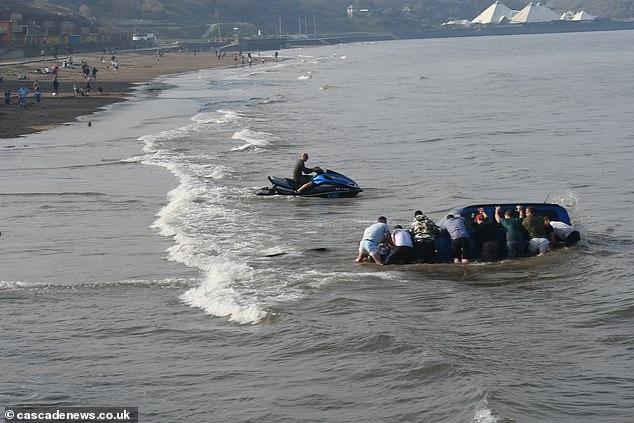Несчастный водитель, который отбуксировал водный мотоцикл на берег, отчаянно пытается вытащить свою машину, а прилив уже начался