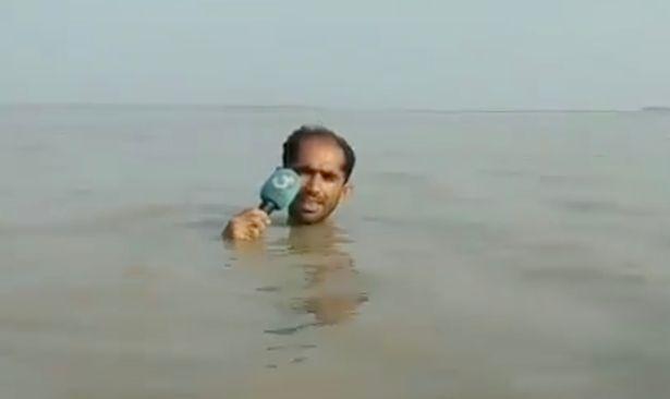 Журналист ведет репортаж в прямом эфире по горло в воде, чтобы показать реальный уровень наводнений